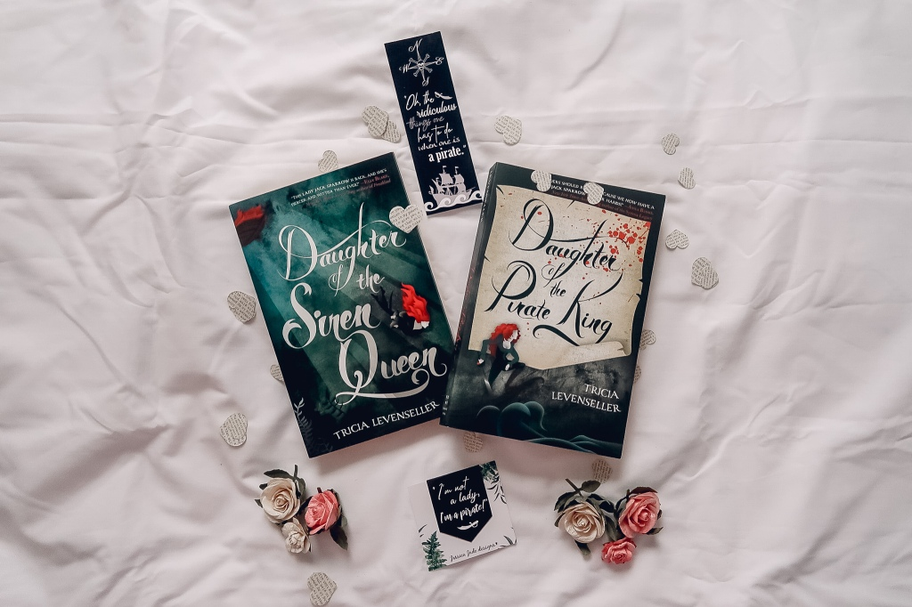 """Daughter of the Pirate King and Daughter of the Sire Queen surrounded by two bookmarks, fake flowers and paper hearts. The first bookmark says, """"I'm not a lady, I'm a pirate!"""" and the second says, """"Oh, the ridiculous things one has to do when one is a pirate."""""""