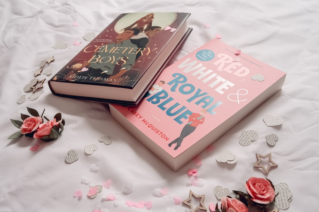 Two books laid out, Cemetery Boys by Aiden Thomas and Red, White & Royal Blue by Casey Mcquiston, surrounded by paper hearts, wooden stars, pink flowers and pink and white confetti hearts.