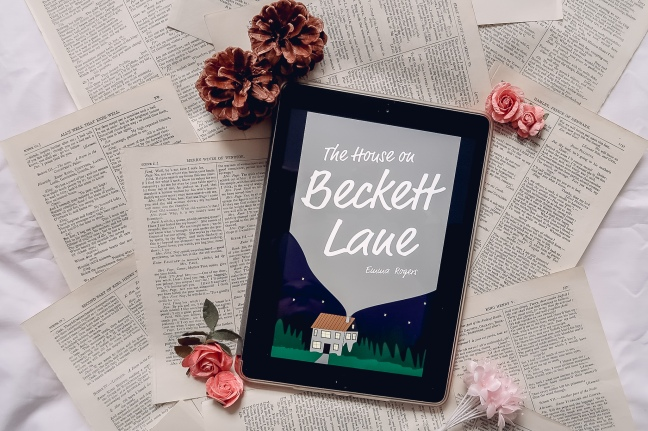 An iPad showing the cover of The House on Beckett Lane with a background of book pages surrounded by fake flowers and pine cones.