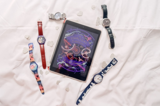 The Starlight Watchmaker cover on an iPad surrounded by 5 watches and white paper hearts.