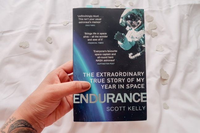 Me holding a copy of Endurance by Scott Kelly with paper hearts in the background