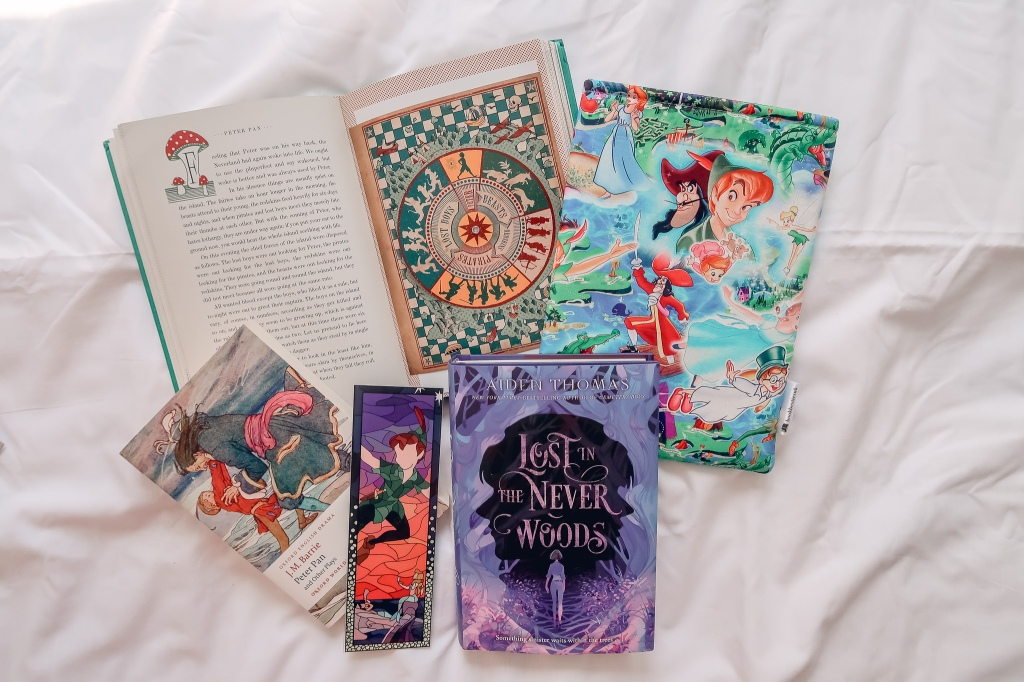Flatlay of two copies of Peter Pan, one open with a moveable circle illustration, a copy of Lost In The Never Woods, a Peter Pan book sleeve and bookmark.