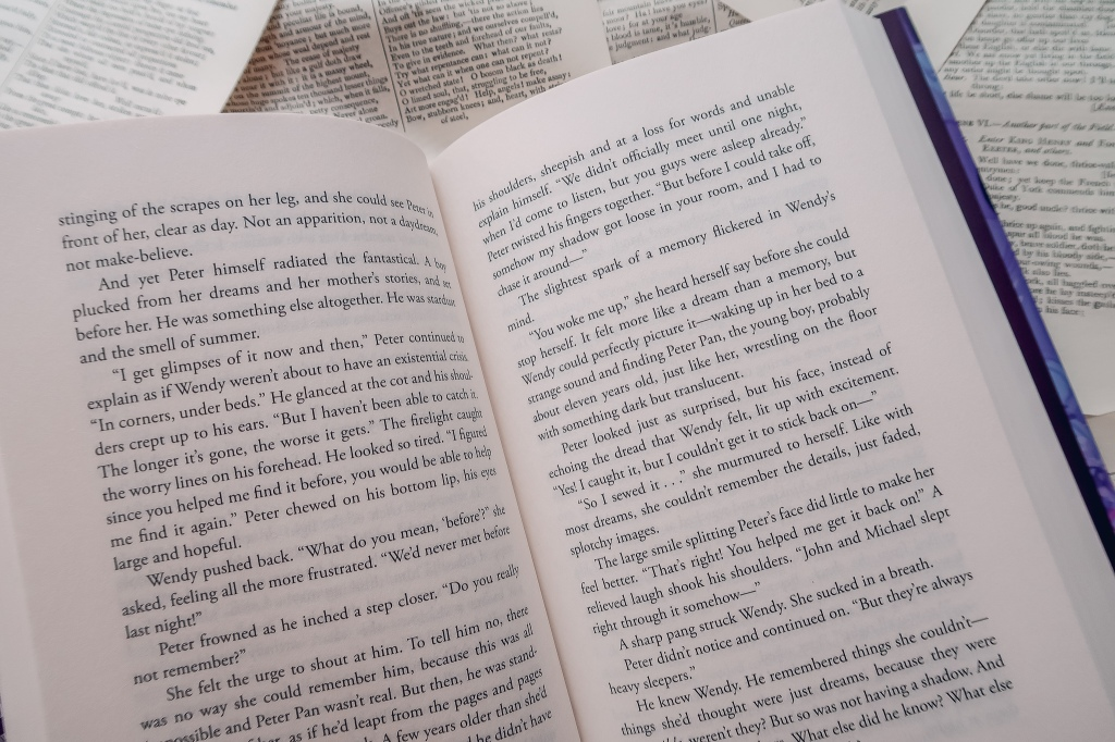 An open copy of Lost In The Never Woods with book pages as a backdrop
