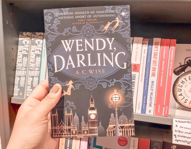 My hand holding a copy of Wendy, Darling in front of book shelves in a bookstore.