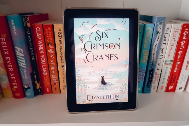 Six Crimson Cranes cover on iPad in front of a book shelf full of books