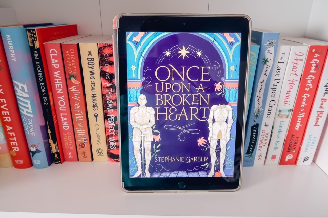 Once Upon A Broken Heart cover on iPad resting on a bookshelf with books lined up in the background.